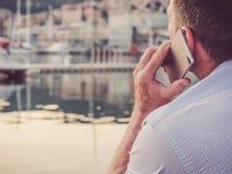 Homme attirant avec une position de téléphone sur le rivage photos stock