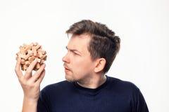 Homme attirant d'affaires de 25 ans regardant confus le puzzle en bois Photographie stock libre de droits