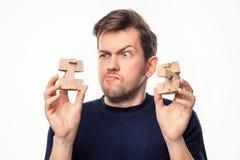 Homme attirant d'affaires de 25 ans regardant confus le puzzle en bois Images libres de droits