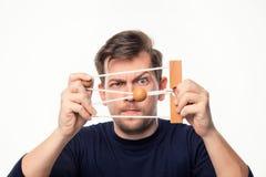 Homme attirant d'affaires de 25 ans regardant confus le puzzle en bois Images stock