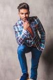 Homme attirant d'affaires tenant sa jambe sur une boîte en bois Photo stock