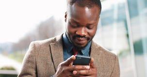 Homme attirant d'Afro-américain à l'aide du smartphone dans la ville Jeunes sms beaux d'homme d'affaires textotant utilisant le s banque de vidéos