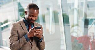 Homme attirant d'Afro-américain à l'aide du smartphone dans la ville Jeunes sms beaux d'homme d'affaires textotant utilisant le s clips vidéos