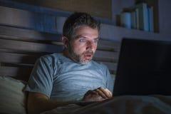 Homme attirant d'intoxiqué d'Internet dans la mise en réseau de choc et de surprise de fin de nuit sur le fonctionnement d'expres images libres de droits