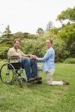 Homme attirant dans le fauteuil roulant avec l'associé se mettant à genoux près de lui Photographie stock