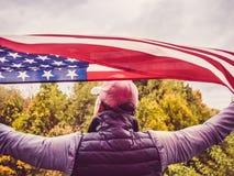 Homme attirant dans une casquette de baseball, tenant un drapeau des USA photographie stock