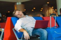 Homme attirant et fatigué de voyageur avec le bagage prenant un petit somme dormant tout en travaillant avec le vol de attente d' photos libres de droits