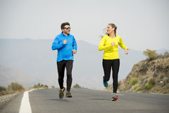 Homme attirant et femme de couples de sport courant ensemble sur le paysage de montagne de route goudronnée Images libres de droits