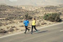 Homme attirant et femme de couples de sport courant ensemble sur le paysage de montagne de route goudronnée de désert Photos stock