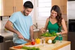 Homme attirant et femme préparant le dîner faible en calories dans la santé de cuisine très consciente Image libre de droits