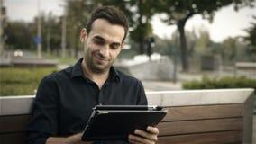 Homme attirant heureux à l'aide de la tablette dehors sur un banc de parc banque de vidéos