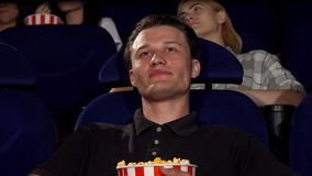 Homme attirant heureux souriant à l'appareil-photo au cinéma banque de vidéos
