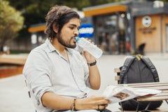 Homme attirant s'asseyant au café de rue, regardant la carte et l'eau potable  images stock