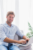 Homme attirant s'asseyant sur le divan et à l'aide de son ordinateur portable Image libre de droits