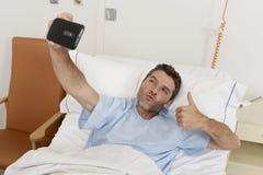 Homme attirant se trouvant sur la clinique d'hôpital de lit tenant le téléphone portable prenant la photo de selfie d'autoportrai Photographie stock