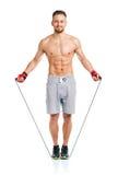 Homme attirant sportif sautant sur une corde sur le blanc Photos stock
