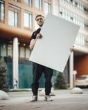 Homme attirant tenant la toile vide à la rue et regardant la visionneuse Photographie stock libre de droits