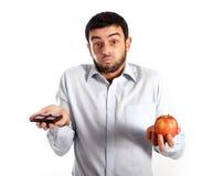 Homme attirant tenant le chocolat et Apple Photographie stock libre de droits