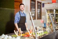 Homme attirant travaillant à un comptoir à salades photos stock