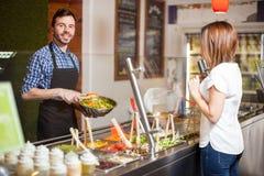 Homme attirant travaillant à un comptoir à salades photographie stock
