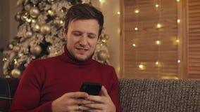Homme attirant utilisant le smartphone se reposant sur le divan, transmission de messages, souriant en appartement décoré près de clips vidéos