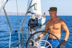 Homme au bateau à voile de barre, les contrôles de bateau pendant la course de yacht de mer sport Photos stock
