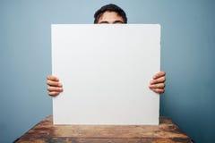 Homme au bureau se cachant derrière un conseil blanc Photos stock