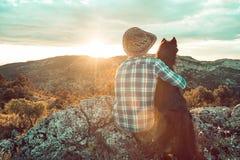 Homme au coucher du soleil étreignant son chien Images libres de droits
