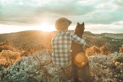 Homme au coucher du soleil étreignant son chien Photos stock