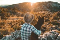 Homme au coucher du soleil étreignant son chien Photographie stock