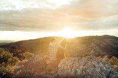 Homme au coucher du soleil étreignant son chien Images stock