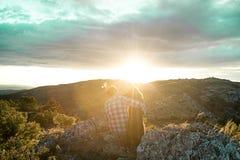 Homme au coucher du soleil étreignant son chien Photo libre de droits