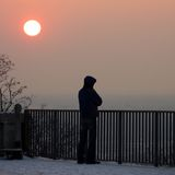 Homme au-dessous de coucher du soleil Image stock