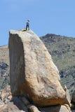 Homme au dessus d'une roche. Photo stock