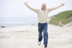 Homme au fonctionnement et au sourire de plage Photographie stock