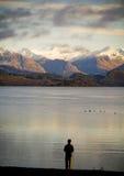 Homme au lac à l'aube images stock
