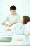 Homme au lit de wifes Photographie stock