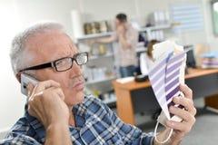 Homme au téléphone tenant des nuanciers semblant sceptiques Photo stock