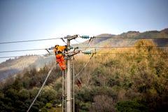 Homme au travail Le technicien réparent les systèmes de transmission à haute tension sur les poteaux de puissance images stock
