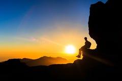 Homme augmentant la silhouette dans la liberté de coucher du soleil de montagnes Photo stock