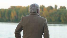 Homme aux cheveux gris appréciant la belle vue de la réflexion d'arbres d'automne en rivière calme banque de vidéos