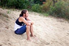 Homme aux pieds nus aux cheveux longs s'asseyant sur la plage regardant au-dessus de t photo libre de droits