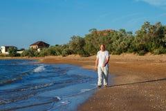 Homme aux pieds nus marchant sur les vagues du ressac image libre de droits