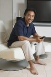 Homme avec à télécommande dans l'écran de Front Of Large TV à la maison Photographie stock libre de droits