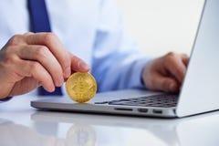 Homme avec Bitcoin et l'ordinateur portable dans le bureau photographie stock