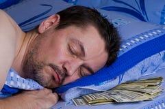 Homme avec de l'argent sous son oreiller image stock