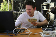 Homme avec de l'argent travaillant sur l'ordinateur Photographie stock libre de droits