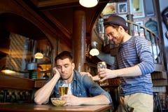 Homme avec de la bière et l'ami ivre à la barre ou au bar Photo stock