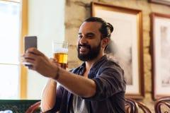 Homme avec de la bière potable de smartphone à la barre ou au bar Image libre de droits