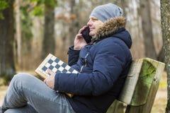 Homme avec des échecs parlant au téléphone intelligent en parc Photographie stock
